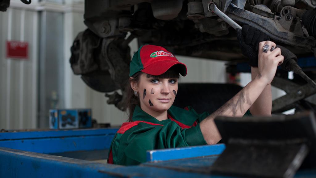 mulher em uma oficina mecânica mexendo em um carro.