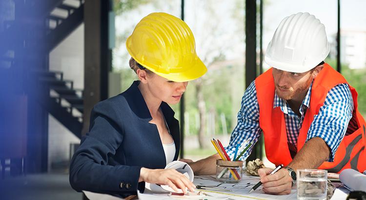 uma mulher de capacete amarelo e um homem de capacete branco conversando e analisando um projeto.