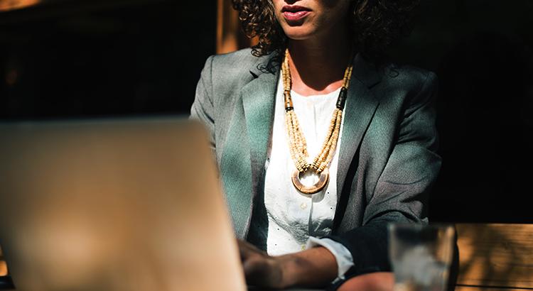 mulher negra sentada, usando um notebook.